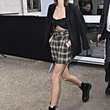 Kaia wearing a black bandeau top with a blazer, plaid shorts, and combat boots.