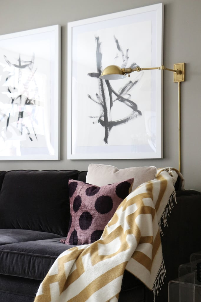 The black-gray sofa reflects Victoria's masculine-glam aesthetic, which is marked by dark, glossy tones and rich, textured fabrics.