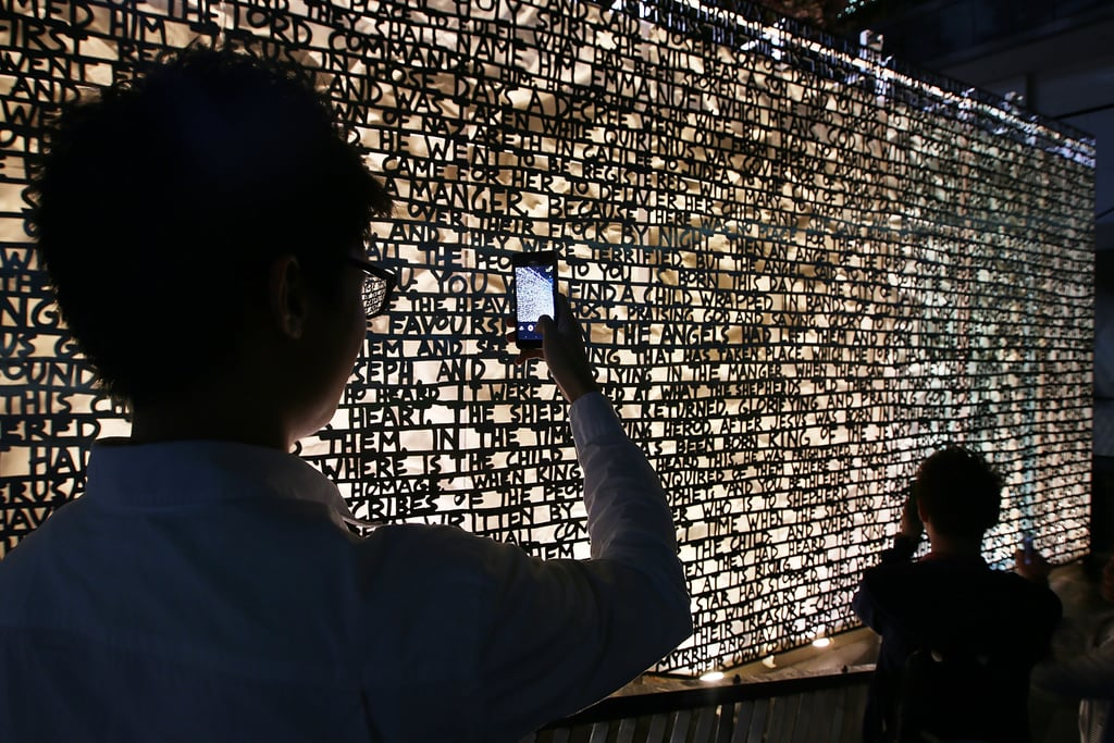Tourists took pictures of the wordy wall that explains the nativity story in Melbourne's Christmas Square.