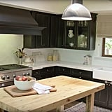 Black cabinets and a reclaimed-wood preparation table make their kitchen the perfect mix of rustic and modern.