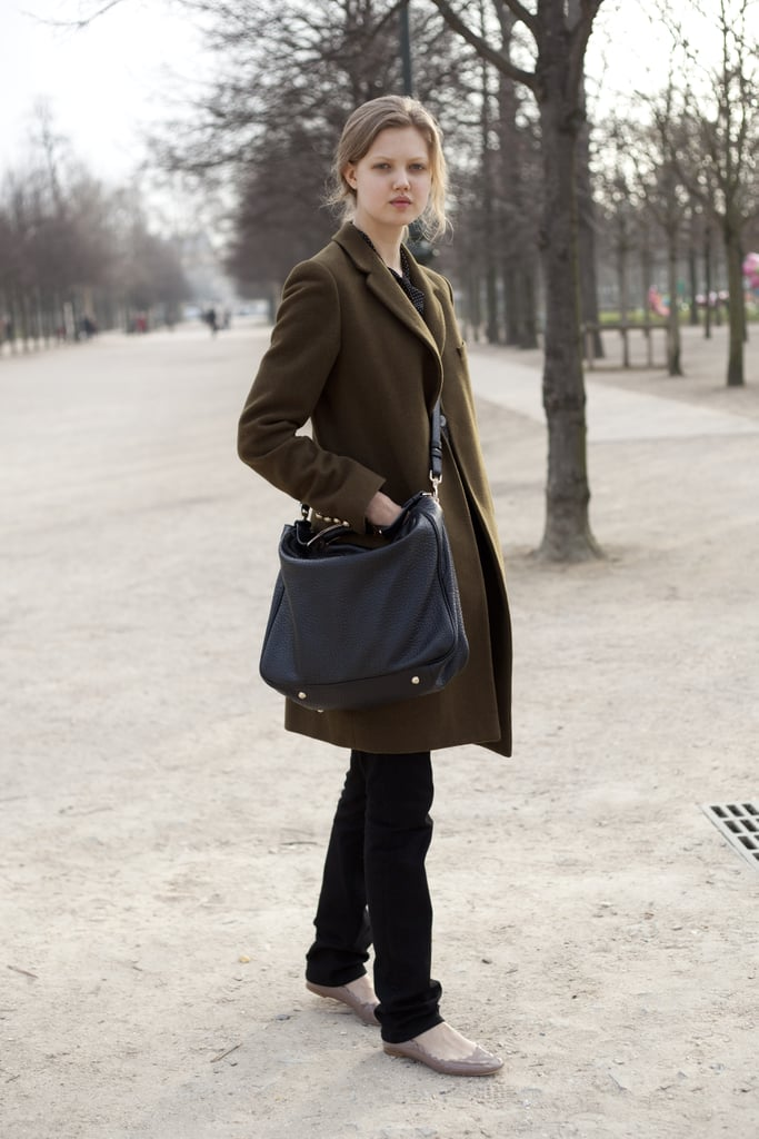 Model Lindsey Wixson pairs scallop-edged nude flats with laid-back add-ons, like a messenger bag and a cosy olive green coat.