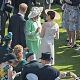 Camilla took Meghan's hand as they spoke while attending Prince Charles's 70th birthday celebration at Buckingham Palace in May.