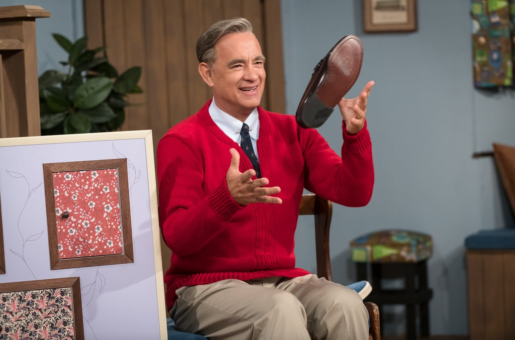 """After even the darkest storms, there's a rainbow, and today it came in the form of a red sweater. On Wednesday, Sony released two new photos of Tom Hanks as Mister Rogers in the upcoming You Are My Friend movie, and we. are. emotional. Not only is Hanks the perfect actor to portray Fred Rogers, but let's discuss how incredible he looks. From the parted hair all the way down to the trademark shoes, we're already nodding our heads in awe over whatever words of wisdom are about to come out of his mouth.  The biopic is inspired by """"the real-life friendship between Fred Rogers and award-winning journalist Tom Junod,"""" and will hit theaters on Oct. 18, 2019. While it's been some time since the final episode of Mister Rogers' Neighborhood aired on Aug. 31, 2001, it's safe to say we could all use a bit of his nurturing energy and positive spirit in our lives. Read on to see how fans are freaking out over the first photos of Hanks as Mister Rogers, and believe that he can turn any crappy climate into a beautiful day in the neighborhood.      Related:                                                                                                           10 Facts About Mister Rogers That Will Put a Smile on Your Face and a Song in Your Heart"""