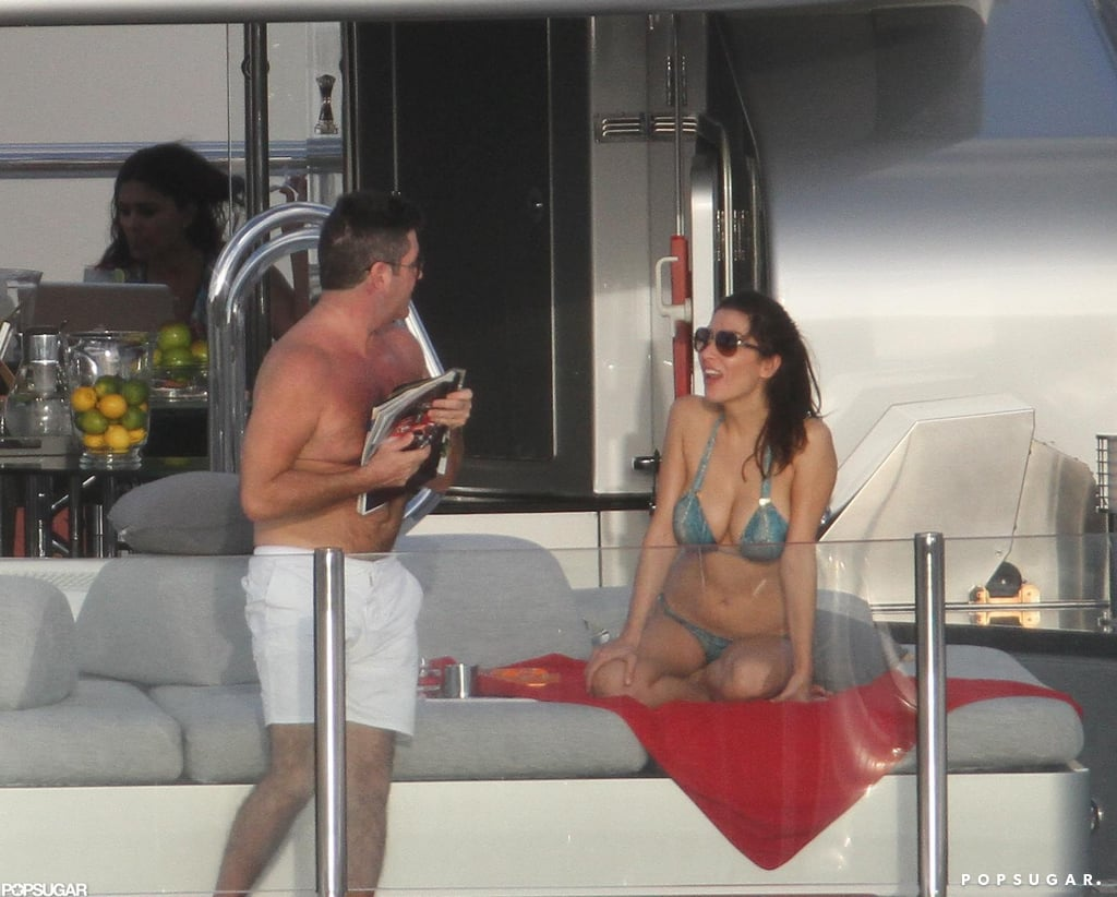 Shirtless Simon Cowell read magazines while Mezhgan Hussainy lounged in a bikini.