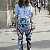 Another major trend outside the shows was decorated denim, which this attendant playfully paired with a fruity crossbody bag.