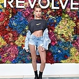 Hailey Baldwin wearing a slashed tee, glitter tights, and denim at the Revolve festival.