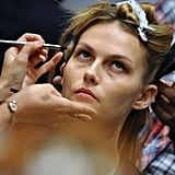 While it may look like the La Perla models were wearing hardly any makeup, we all know that the no-makeup look can take a lot of work! Backstage the makeup team applied creamy-neutral colours to the eyes and evened out the base for a flawless look.  Source