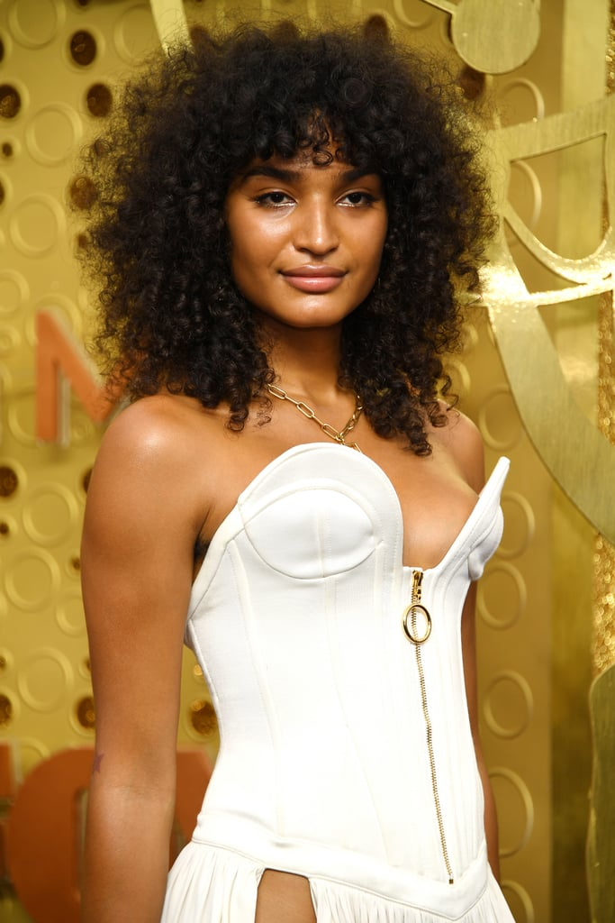 "Model and actor Indya Moore arrived at the Emmy awards looking stunning with a head full of curls and natural-looking makeup. The Pose star's curls took center stage as they left the rest of their makeup natural and glowy, with a small amount of gold eye shadow on the inner corners of their eyes and rose-colored gloss applied by makeup artist Elyse Thoms for Pat McGrath Labs.  The golden eye shadow was courtesy of the brand's Midnight Sun Eyeshadow Palette ($125) in the shade ""Astral Solstice,"" and Moore wore Lust Gloss ($30) in the shade ""Flesh Fantasy"" on their lips.  Ahead, check out Moore's curls and makeup from every angle. Editor's note: This post has been edited from its original version, which incorrectly referred to Moore's curls as a ""shag haircut."""