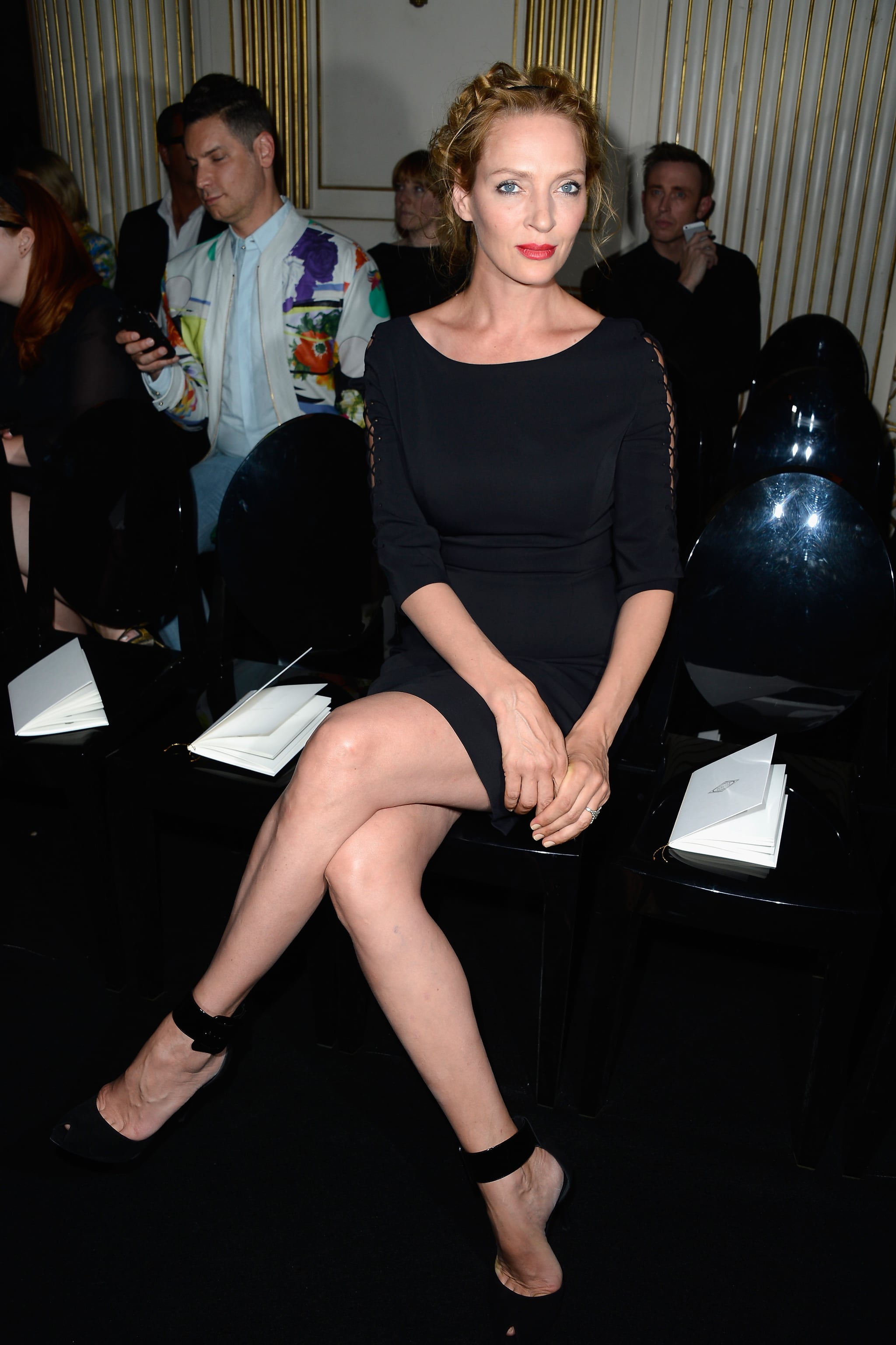 Uma Thurman took in Versace's couture show in all black. She put her long legs on display in a little black Versace dress and sexy ankle-strap pumps.