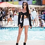 Shay Mitchell wearing a black tie-front top with a pair of Grlfrnd Denim high-waisted shorts and Five and Two Jewelry.