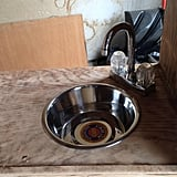 They used a metal dog bowl for a sink and glued on a faucet.