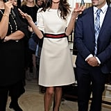 This little A-line midi is so cute. Amal keeps it minimal with a red belt and black pointed-toe stilettos.