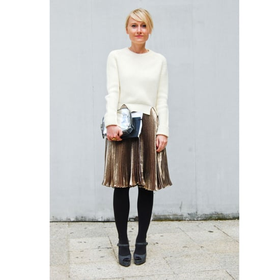 """A gold pleated skirt — spotted on the street during Spring 2012 Paris Fashion Week — looks chic for day when topped with a cozy cream sweater and opaque black tights. Gray Mary Janes keep the look soft, and a silver Alexander Wang clutch adds contrast.   Shop the look: <iframe src=""""http://widget.shopstyle.com/widget?pid=uid5121-1693761-41&look=4300507&width=3&height=3&layouttype=0&border=0&footer=0"""" frameborder=""""0"""" height=""""244"""" scrolling=""""no"""" width=""""286""""></iframe> Photo: Stylesight"""