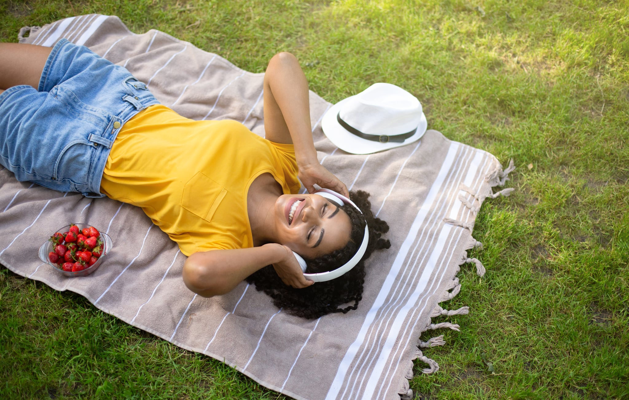 Above view of beautiful African American woman with headphones listening to music during picnic at park