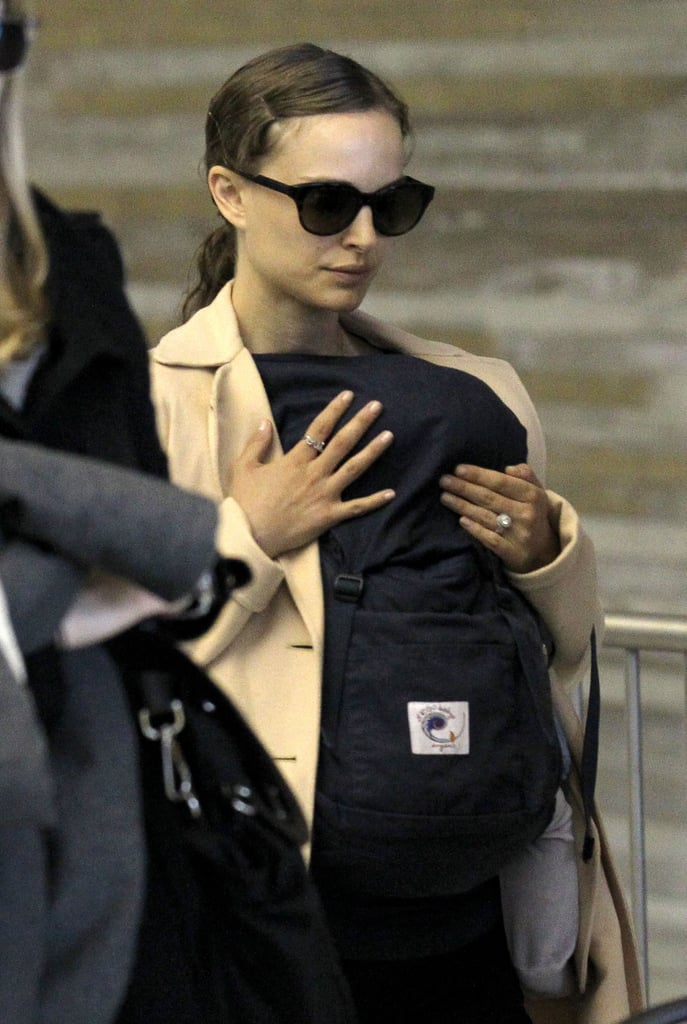 Natalie Portman with baby Aleph in a carrier at the airport in Paris.