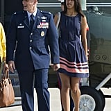 Wearing a navy tank dress with salmon stripes.