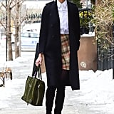 Karlie Kloss gave off preppy vibes thanks to a crisp, white button down tucked into a plaid-printed skirt. She kept warm with tights and over-the-knee boots.