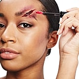 On top of the black eyeliner, add red lipstick and a deep brick lip gloss. This gives the wound a wet, oozing look.