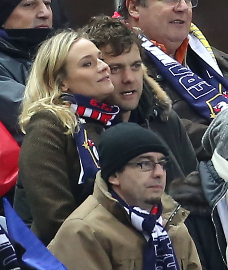 Diane Kruger and Joshua Jackson huddled close to one another in the stands of a soccer game in Paris.