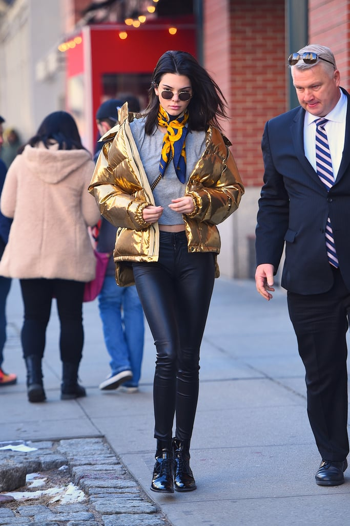 Kendall Jenner styled her metallic Ports 1961 puffer jacket with a gold silk scarf.