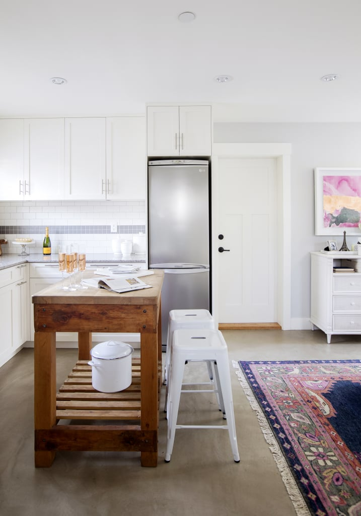 """With a practical wooden island and on-trend industrial-chic stools, the kitchen embodies Jillian's """"fresh, clean, and functional aesthetic."""""""