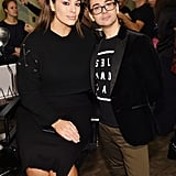 Wearing a black sweater and skirt while standing next to designer Christian Siriano before the show.