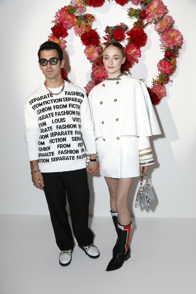 """It's been a while since Sophie Turner and Joe Jonas last rocked a red carpet, but they sure didn't forget how to show up in style. In fact, the couple looked cool as ever at a Louis Vuitton dinner in Paris celebrating the Les Extraits fragrance collection on July 5. While the new parents wore matching black-and-white looks and, of course, head-to-toe Louis Vuitton, they still remained true to their personal styles — Sophie opted for an edgy yet sophisticated outfit, while Joe went with his usual bold, sporty pieces.  Sophie's ensemble consisted of a white leather cape coat with gold and silver accents, pointed boots, and the new silver Coussin bag. Joe, on the other hand, sported a graphic white sweater with lettering that read """"Separate fashion from fiction"""" with black pants, white sneakers, and dark shades. He jazzed up the simple outfit with a rainbow chain necklace and matching bracelet, as well as colorful shoelaces.  The fragrance dinner marks the couple's first red carpet since welcoming their daughter, Willa, last July. Sophie and Joe were among fellow new parents Katy Perry and Orlando Bloom, as well as stars like Bella Hadid, Florence Pugh, and Joan Smalls. Get a closer look at the cool duo's coordinated looks ahead.       Related:                                                                                                           Sophie Turner's 14 Best Fashion Moments in Louis Vuitton"""