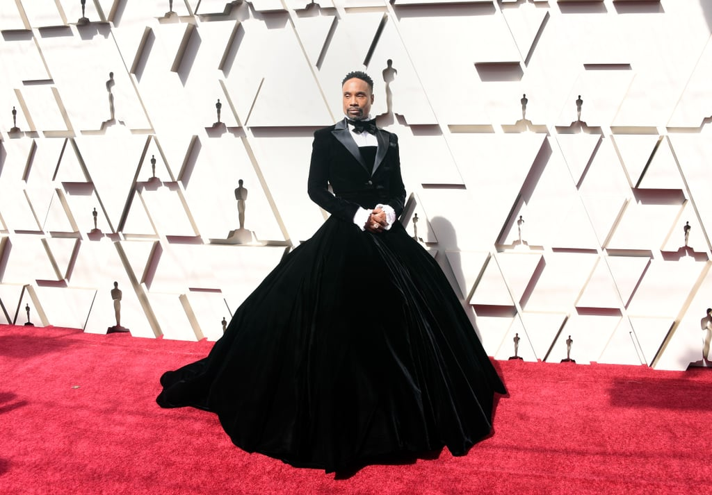 "File this look under: show-freakin'-stopper. Billy Porter may not be nominated for any awards at the 2019 Oscars, but he showed up on Sunday night ready to turn heads. The Pose star arrived on the red carpet with husband Adam Smith in an incredibly fabulous custom Christian Siriano velvet tuxedo gown. Yep, business on the top and magnificent on the bottom. After posing for photos in the ballroom gown, Billy wore a tailored velvet skirt as he hosted a red carpet show.  The stunning look is not at all out of character for Billy. After pulling up to the Golden Globes earlier this year wearing a pink cape, Billy ""had the courage to push the status quo,"" he told Vogue about his Oscars look. ""My goal is to be a walking piece of political art every time I show up. To challenge expectations. What is masculinity? What does that mean? Women show up every day in pants, but the minute a man wears a dress, the seas part. . . We wanted to play between the masculine and the feminine. This look was interesting because it's not drag. I'm not a drag queen, I'm a man in a dress."" He added, ""People are going to be really uncomfortable with my black ass in a ball gown — but it's not anybody's business but mine."" Well, he looked spectacular to us, and he even honored ballroom legend Hector Xtravaganza with his gown. See photos of Billy's Siriano look ahead, and prepare to be wowed. Related: These Oscars Gowns Are So Damn Sexy, We Don't Know What to Do With Ourselves"