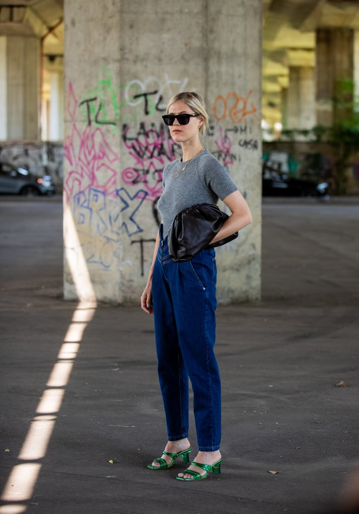 Wear a Pair of Dark Denim '80s-Style Trousers With Metallic Sandals and a Gray Tee