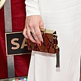 Maggie Gyllenhaal's Fred Leighton ring played up her square statement box clutch, which was complete with a small tassel.