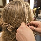 You can create a small French braid that drapes down and connects to the larger braids, or just a regular small braid (as pictured here).