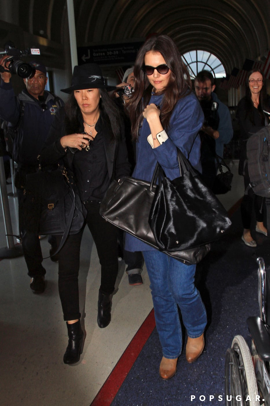Katie Holmes and Jeanne Yang made their way through LAX on Wednesday.