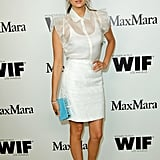 Nina Dobrev paired her dress with a bright blue clutch.