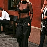 Rita Ora showed off her scalloped black bra — and lots of cleavage — under her sheer turtleneck. She finished her outfit with black tie-waist pants and some go-to accessories: pearl earrings, oversize sunglasses, and a gold pendant necklace.