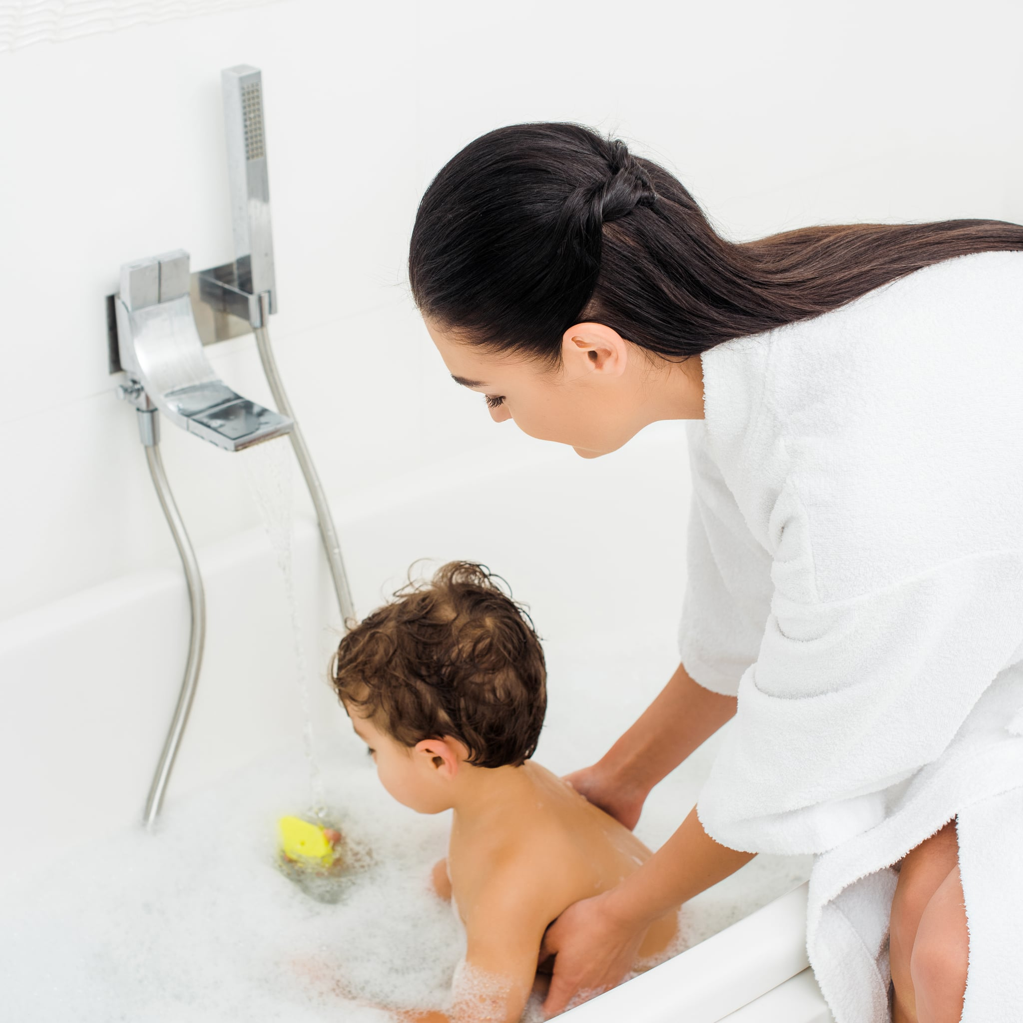 Mom in bathrobe washing son in white bathroom; Shutterstock ID 1234308316; Job: -