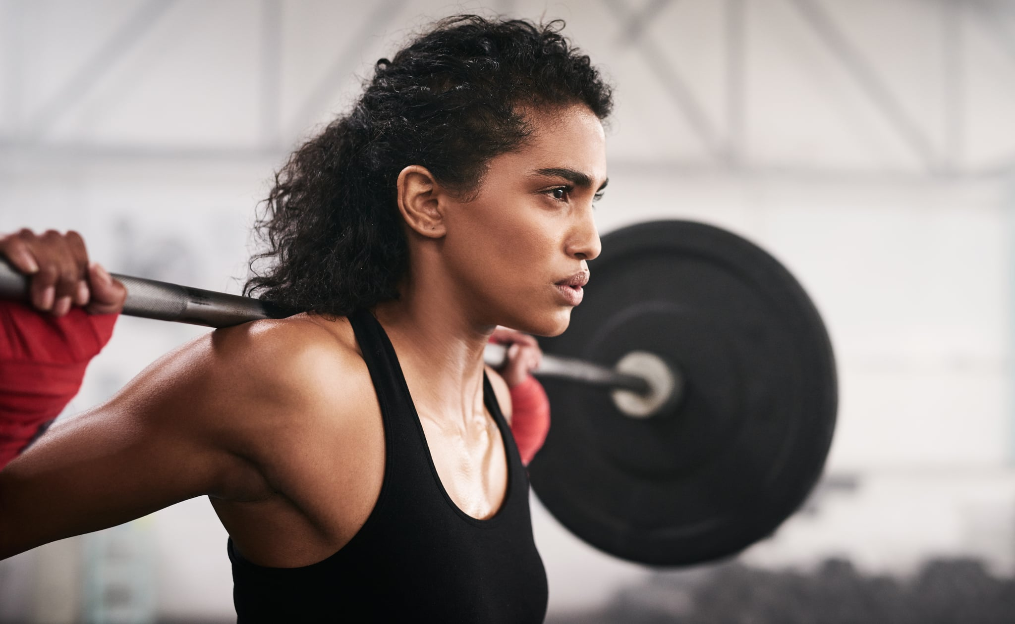 Shot of a sporty young woman lifting a barbell in a gym