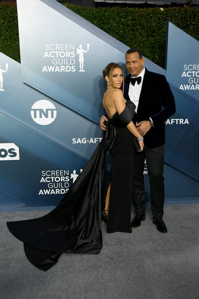 Jennifer Lopez showed up to the SAG Awards on Sunday night looking sleek, sexy, and suave in a Georges Hobeika gown. The 50-year-old actress is nominated for her role in Hustlers and she looked every inch a winner in her outfit, styled by Rob Zangardi and Mariel Haenn.  The black off-the-shoulder dress featured a dramatic bow detailing in the back (there's something about bows for J Lo this season!) and an extended train, which she got a little help fixing on the red carpet. Jennifer tied the whole look together with a glittering necklace, earrings, and a bracelet from Harry Winston, as well as her massive engagement ring from fiancé, Alex Rodriguez. Keep reading to see more of J Lo's award show ensemble.
