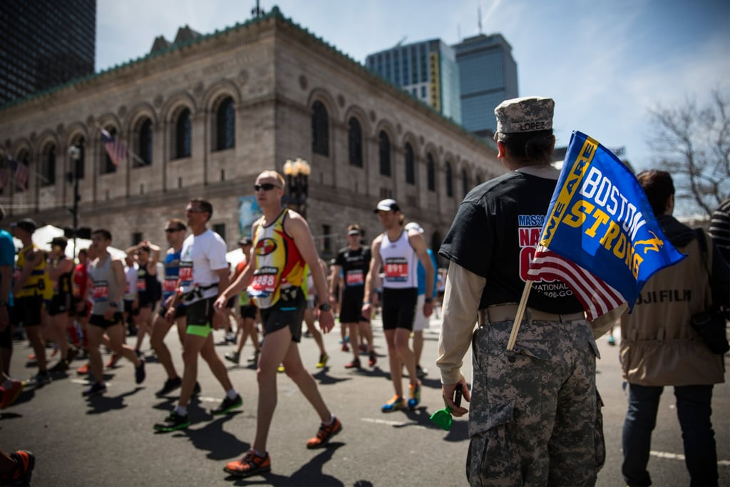 "A soldier held a ""Boston strong"" flag while cheering on the runners."
