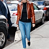 Selena wore her brown Coach moto jacket again while out in NYC. This time she paired it with cropped skinny jeans, a black sweater, and black mules.