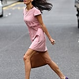 A mad dash across the street looked as graceful as ever in a pastel shift dress and quirky heels.