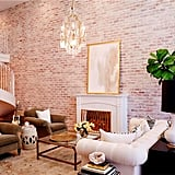 The two-story living room is striking not only for its soaring height but also for the custom spiral staircase and 20-foot reclaimed brick accent wall.