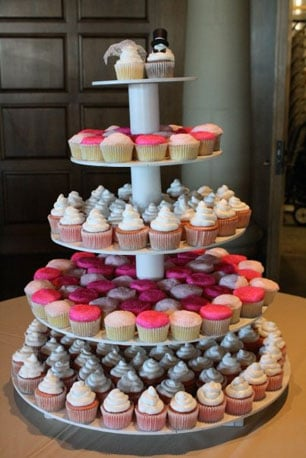 While the girlie pink, sparkly, and shimmery cupcakes on this wedding tower tickled my fancy, it's the bride and groom that really won me over — there's even a tiny blue button on the bride for her something blue! Photo by Lisa Pearce