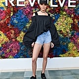 Kendall Jenner wearing a puff-sleeved top and denim shorts at the Revolve festival.
