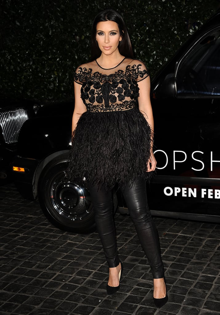 Kim Kardashian looked slick in leather leggings and an feather-embellished, peplum-inspired top.
