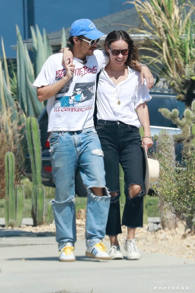 """Harry Styles and Olivia Wilde have been spotted wearing coordinated outfits, and we love them for it. The couple was seen wearing similar outfits while taking a stroll in Los Angeles with their arms around each other. The """"Watermelon Sugar"""" singer and Booksmart director looked adorable smiling in their classic summer outfits consisting of a baggy white tee, ripped jeans, and trainers.  Harry, who has been linked with Olivia since starring in the director's upcoming movie Don't Worry Darling, wore an oversized Beastie Boys band t-shirt, which he paired with baggy jeans that had rips around the knees. He also wore white Adidas sneakers, a blue baseball cap, and '70s-inspired white sunglasses. On the other hand, Olivia also wore a baggy white tee paired with dark-washed baggy jeans that also had rips on the knees. Her accessories differed with a pair of black aviator sunglasses, a wide-brimmed hat, and a gold necklace.  By the looks of it, we have a feeling this isn't the last stylish couple's outfit we're going to be seeing from the duo in the near future.       Related:                                                                                                           We Wanna Look as Carefree as Harry Styles in Italy Wearing This Outfit on a Boat"""