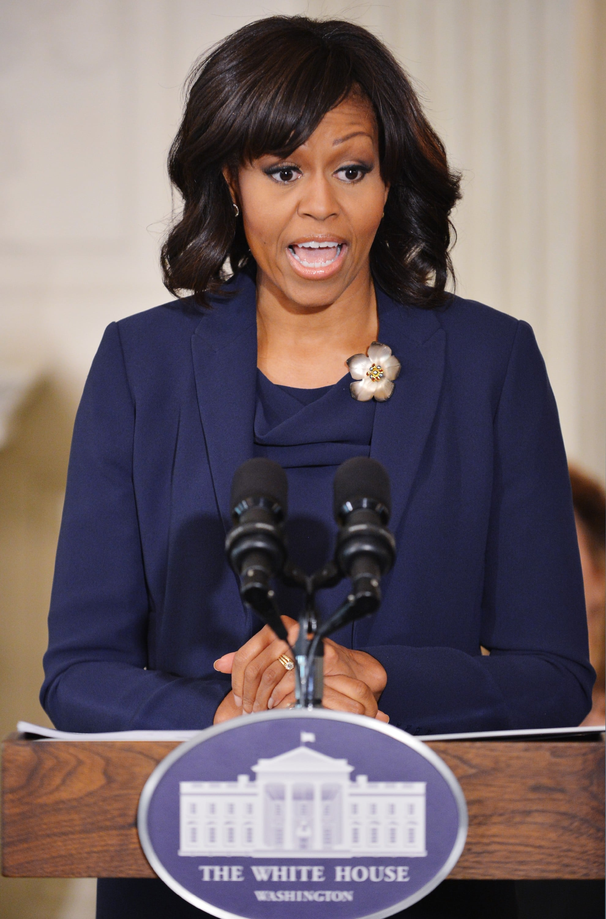 She accented a navy blue suit with an ultrafeminine floral brooch.