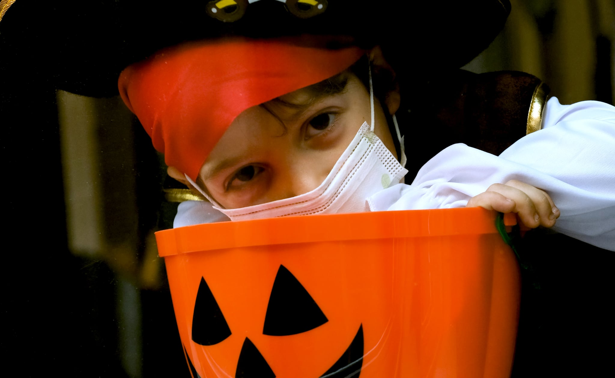 Sad little boy wearing a halloween pirate costume and a protective face mask looking through a window holding a Jack o Lantern bucket