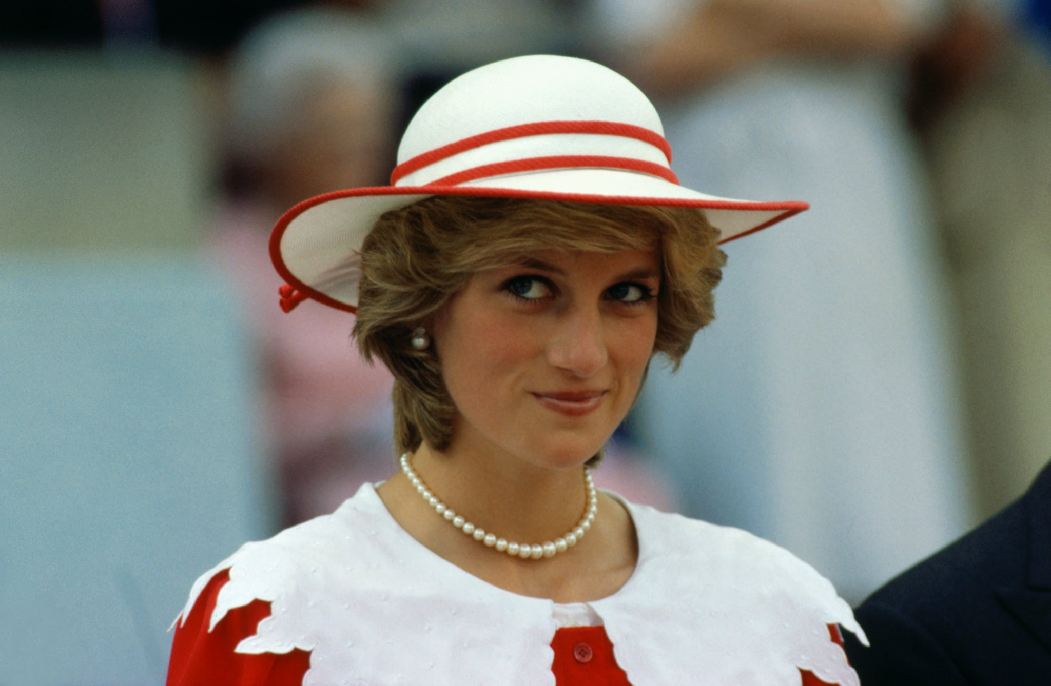 Diana, Princess of Wales, wears an outfit in the colours of Canada during a state visit to Edmonton, Alberta, with her husband.