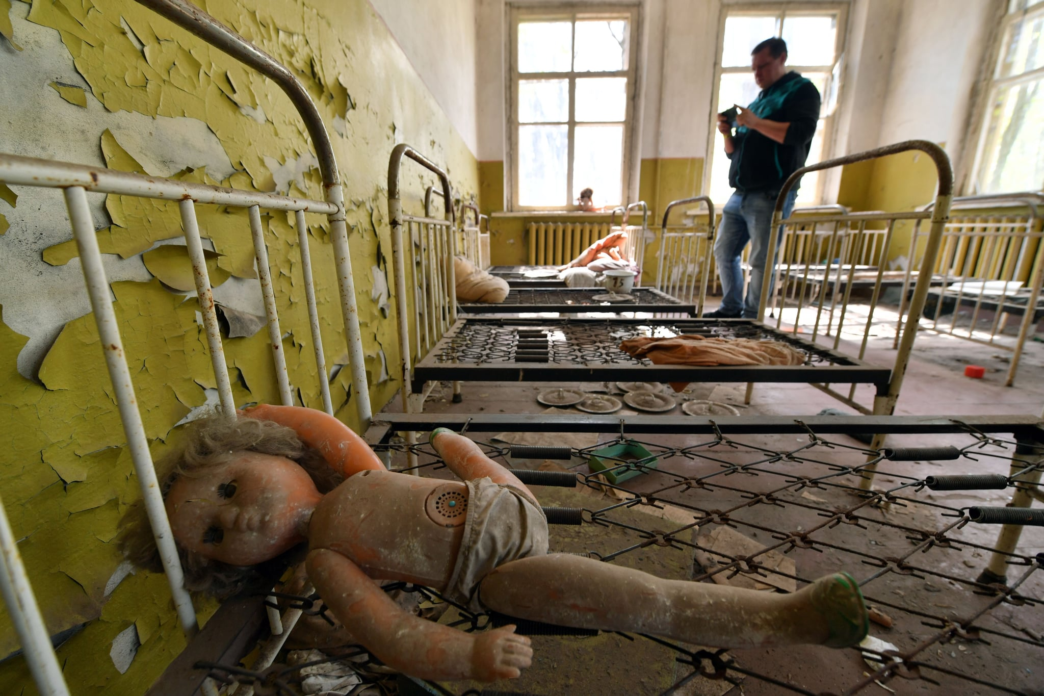 TOPSHOT - A tourist takes a picture in an abandoned kindergarten in the ghost village of Kopachi near Chernobyl Nuclear power plant during their tour to the Chernobyl exclusion zone on April 23, 2018. - Ukraine on April 26, 2018 will mark the 32nd anniversary of the Chernobyl disaster which was the world's worst nuclear accident. (Photo by Sergei SUPINSKY / AFP)        (Photo credit should read SERGEI SUPINSKY/AFP/Getty Images)