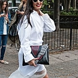 This fashionista added some contrast to a white dress with a precious pouch.